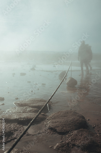 Fotografia, Obraz People walking through the cloud of steam from the erupted geyser