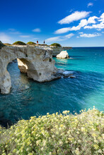 Tourists Admiring The Sea From Natural Stone Arch On Cliff, Torre Sant'Andrea, Lecce Province, Salento, Apulia, Italy