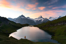 Hiker Admiring Sunrise From The Shores Of Bachalpsee Lake, Grindelwald, Bernese Oberland, Bern Canton, Switzerland
