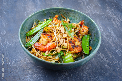 Modern style traditional Thai phak kung curry with barbecue king prawns and noodles as close-up in Nordic design bowl with copy space