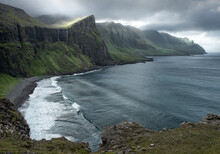 View Over A Hidden Bay With The Sun Filtering Through The Clouds, Faroe Islands, Denmark