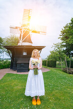 Woman Dressed On Traditional Dutch Dress, Wooden Shoes Yellow Clogs Klompen Holding Bouquet Of Chamomile Flowers With Windmill On Background. Retro Vintage And Countryside Netherlands Concept.
