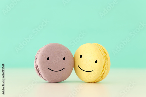 colorful macaron or macaroon with happy face on wooden mint background