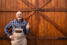 Portrait Of Smiling Farmer Holding Thumbs Up And Standing By Wooden Barn Doors At Animals Farm.