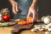 Chef In A Blue Apron Is Cutting Appetizing Fresh Tomatoes With A Knife To Prepare A Dish. Concept Of The Cooking Process