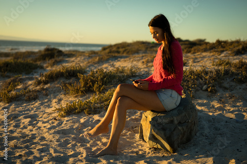 Caucasian woman sitting on rock at beach using smartphone