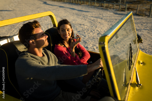 Caucasian couple sitting in beach buggy by the sea during sunset talking by phone