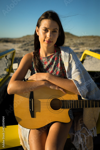 Portrait of happy caucasian woman on the beach holding guitar looking to camera