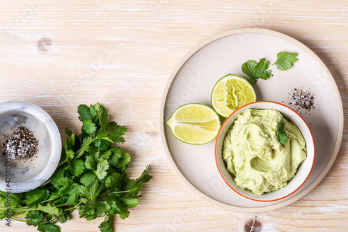 Photo Avocado hummus dip on rustic wooden table, top view