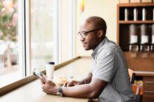 Black Man Using Digital Tablet In Coffee Shop