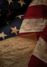Close-up Of Declaration Of Independence Resting On American Flag