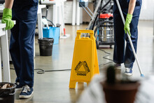 Cropped View Of Wet Floor Signboard Near Cleaners Working In Office