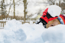 Boy (6-7) Hiding Behind Pile Of Snow And Holding Snowball