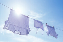 Low Angle View Of Laundry Drying On Clothesline Against Sky And Sun