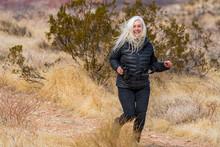 United States, Utah, Zion National Park, Senior Woman Jogging In Desert