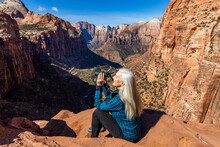United States, Utah, Zion National Park, Senior Woman At Overlook Above Zion Canyon In Zion National Park