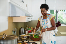 African American Woman Mixing Salad In Kitchen