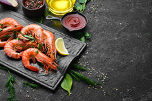Boiled Shrimp With Parsley And Lemon On A Black Stone Plate. Top View. Seafood.