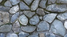 Masonry From Natural Rough Cobblestones With Mossy Winding Seams, Gray-blue Rough Stone In The Structure Of The Fragment Of The Exterior, Part Of The Decor Of The Street Space Made Of Large Stones