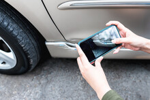 A Woman Using A Mobile Phone Take Photos Of The Damage Of The Car, Which Caused By A Crash Accident As Evidence For Insurance Agents, To People And Transportation Insurance Concept.