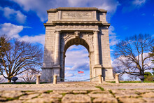 The National Memorial Arch Stands With The American Flag Blowing In The Middle At Valley Forge National Park In Pennsylvania.