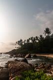 Fototapeta Fototapety z morzem do Twojej sypialni - Skalne wybrzeże na tle oceanu, fal i palm o zachodzie słońca.