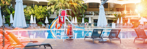 Photo Water pool with umbrellas and recliners on tile floor at hotel area
