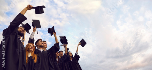 Millennial students celebrating graduation ceremony and throwing their caps up outdoors, copy space text. Young people on commencement day