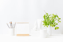 Home Interior With Decor Elements. Mockup White Desk Calendar And Branches With Green Leaves In A Vase On A Light Background