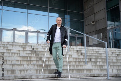 Fotografering Smiling handsome man stands on the stairs with crutches.