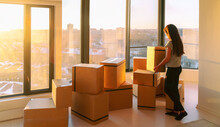 Moving Into New Home Movers Pick-up Service. Woman Ready To Move From Apartment With Belongings Packed In Many Cardboard Boxes Packages For Shipping.