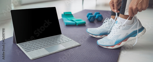 Fototapeta Online fitness class at home banner. Woman getting ready to train hiit workout with laptop screen for streaming. Tying her shoe laces panoramic. obraz