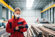 canvas print picture Portrait of a manager in manufacturing hall looking at digital tablet.
