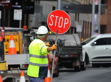 Male Construction Road Worker Holding A Stop Sign And Directing Traffic On The Street. Traffic Management