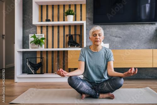 Obraz na plátně Senior woman sitting in lotus pose on yoga mat meditating at home