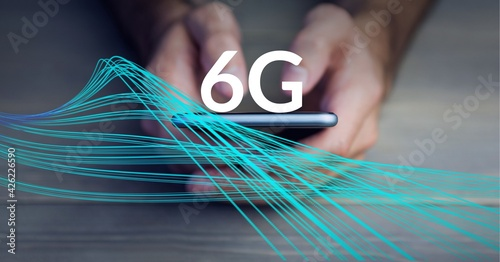 Composition of the word 6g over blue lines and a person holding a smartphone in background