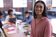 Portrait Of Mixed Race Businesswoman In Meeting Room Looking To Camera Smiling