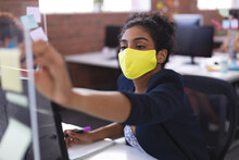Mixed Rase Businesswoman Wearing Mask Sticking Note On Glass Wall