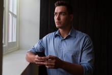 Portrait Of Stylish Caucasian Businessman Thinking Through Window Holding Smartphone
