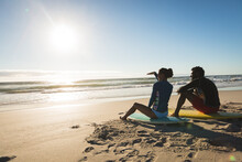 Happy African American Couple On The Beach Sitting On Surfboards Looking Toward Sea