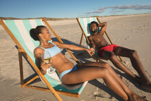 African American Couple In Love Sitting In Deckchairs, Holding Hands On Beach