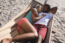 Happy African American Couple Lying In Hammock On The Beach Embracing