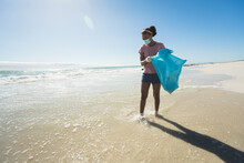 African American Race Woman Wearing Face Mask Collecting Rubbish From The Beach