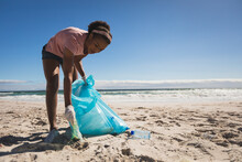 African American Woman Wearing Latex Gloves Collecting Rubbish From The Beach