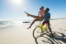 Happy African American Couple Riding Bicycle On The Beach