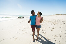 Happy African American Couple On Beach By The Sea Embracing