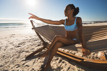 Happy African American Woman Sitting In Hammock On Beach Pointing