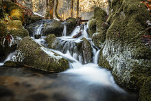 Small Waterfall Over Mossy Rocks In A Forest