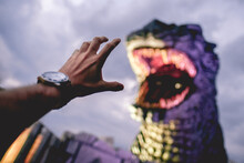 Hand With A Watch And An Amazing Giant Godzilla (Gojira) Statue And The Tokyo Skyline In The Sunset Whit A Cloudy Sky, Japan