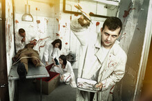 Guy Having Fun With Friends In Quest Room Stylized As Surgical Room With Traces Of Blood, Frightening With Medical Instruments On Camera